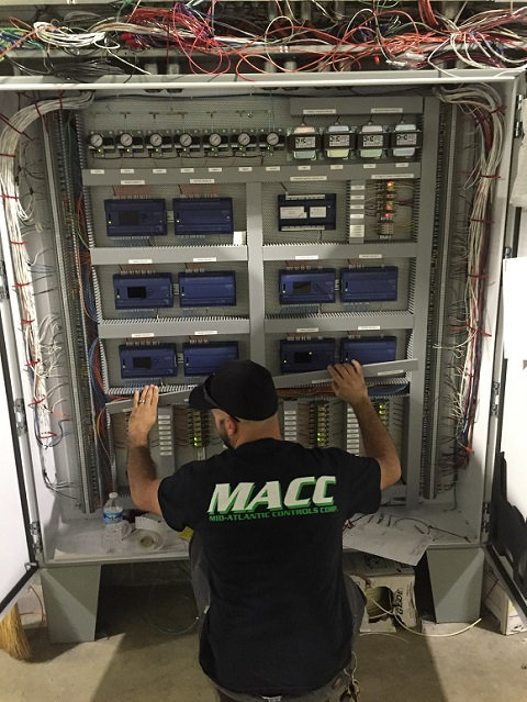 Technician performing maintenance on a BAS system