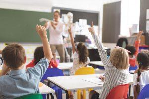 Children in school raising their hands