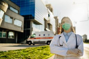 Healthcare worker in front of hospital